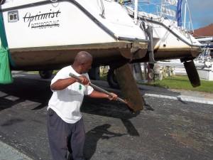 Derwood scrapes the boat hull