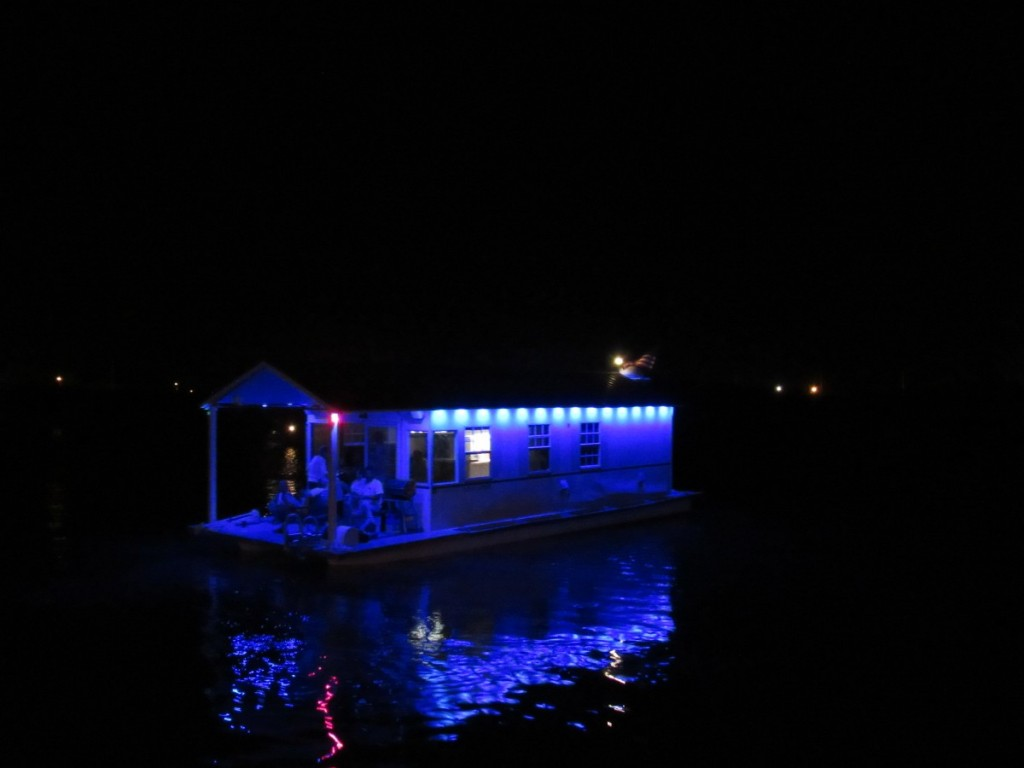 Lit-up house boat pulled by the restaurant / bar to see the happenings
